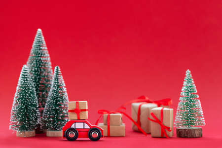 Festive composition Christmas red car with a gift box in a pine forest where many different presents on red background. Happy New Year card concept.