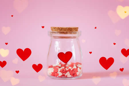 Red hearts in jar on pink pastel background. Valentines day or Mothers day concept, sweet love.