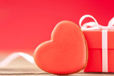 Closeup red gift box with red heart shaped gingerbread for Valentines Day, Mother Day or Birthday on red background.