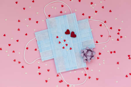 Medical protective masks against  in valentine's day concept with small red hearts on pink background, top view, copy space.