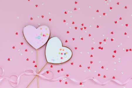 Two pink and white hearts shaped gingerbread for Valentines Day, Mother Day or Birthday on pink background. Flatlay
