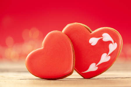 Closeup two red hearts shaped gingerbread for Valentines Day, Mother Day or Birthday on red background.