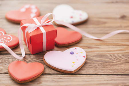 Heart shaped cookies with gift box for Valentine's day or Mother's day on wooden background. Holiday concept.
