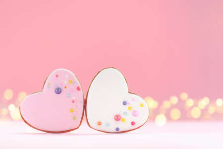 Two pink and white hearts shaped gingerbread for Valentines Day, Mother Day or Birthday on pink background.