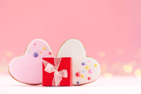 Red gift box with two hearts shaped gingerbread for Valentines Day, Mother Day or Birthday on pink background.