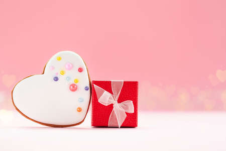 Red gift box with white heart shaped gingerbread for Valentines Day, Mother Day or Birthday on pink background. Stock Photo