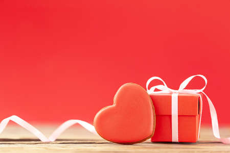 Red gift box with red heart shaped gingerbread for Valentines Day, Mother Day or Birthday on red background.