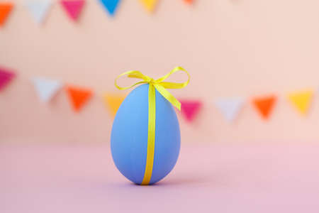 Easter holiday concept with colorful decorate Easter blue egg with copy space on pink background.