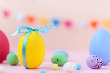 Easter holiday concept with colorful decorate Easter yellow egg with copy space on pink background.