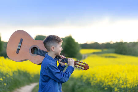 Portrait handsomeboy with guitar walking in the summer yellow field. Young musician on the road to success.