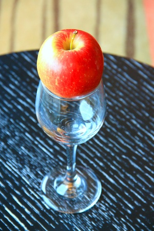 Red apple and empty glass on the table photo