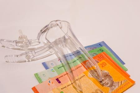 Espéculo médico com notas de banco isolado no branco Foto de archivo - 86670742