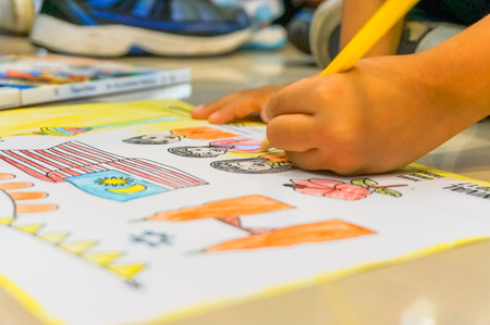 coloring contest.kid is coloring the picture Banque d'images