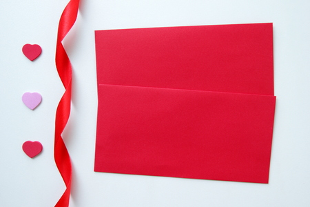Two red envelopes with three hearts and ribbon for Valentines Day.