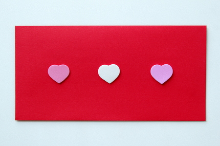 The red envelope with three hearts for Valentines Day. Stock Photo