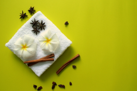 White towel with flowers of plumeria with stars of anise and cinnamon sticks on the yellow background for spa theme.