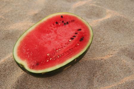 kohl: Travel to Koh Lanta, Thailand. A watermelon on the sandy beach on the sunset.