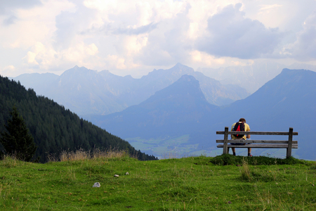 wolfgang: Travel to Sankt-Wolfgang, Austria. The young man are sitting on a bench with view on the mountains. Stock Photo