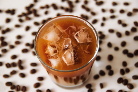 A glass of ice coffee with milk on the white background with coffee beans. Stock Photo