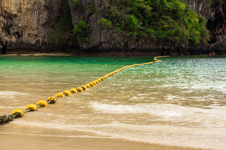 phra nang: Travel to Krabi, Thailand. The scenic view on the sea with yellow buoys and a rock from Phra Nang Beach. Stock Photo