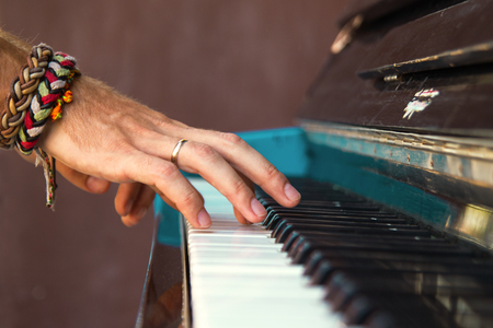 frederic chopin: The hands of a young man playing piano on a street of city.