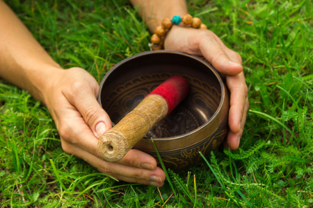 tibetian: The hands of a young woman on tibetian singing bowl with wooden stick on the grass.