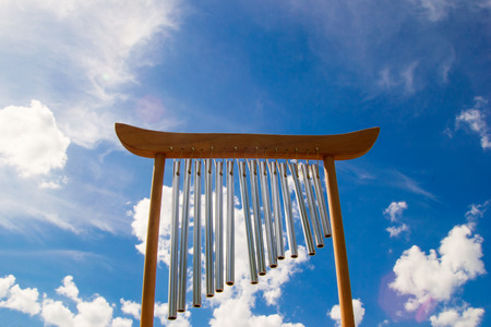 Wind musical chimes on the background of blue summer sky. Stock Photo
