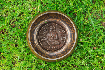 Tibetian singing bowl on the grass, top view