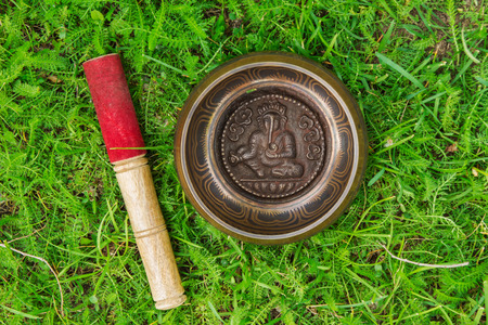 Tibetian singing bowl with wooden stick on the grass, top view.
