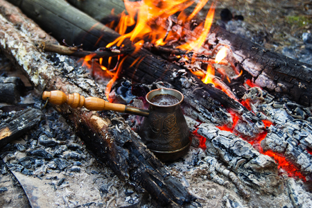 Metal cezve with hot coffee on a bonfire. Stock Photo
