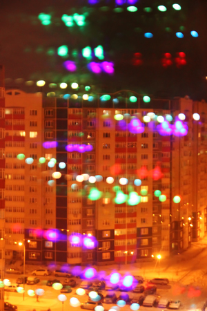 The view from a window on the houses with colorful lights in New Year's night.
