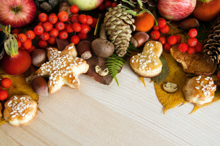 Colorful autumn leaves, mushrooms, rose hips, rowanberry, apples, nuts, cones and cookies on the wooden background. Fall background. Stock Photo