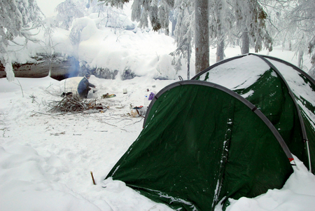 Green tent on a campsite in a winter forest near to mountains. Ural, Russia.