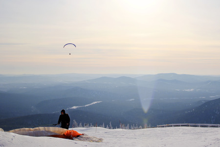 Travel to Sheregesh, Russia. Paraglider is preparing for takeoff near to mountains. Winter landscape. Stock Photo