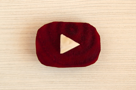 Tyumen, Russia - September 02nd, 2017: Youtube logo made from pieces of beetroot and cabbage on the white wooden background, top view.
