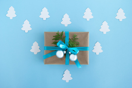 Gift box wrapped of craft paper, blue ribbon and decorated fir branches and silver Christmas balls on the blue background with white paper fir tree, top view. Christmas present. Stock Photo