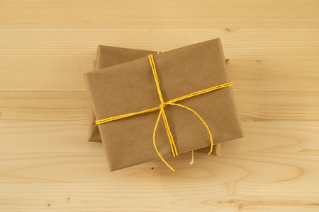 Two gift boxes wrapped of craft paper and yellow ribbon on the wooden background, top view. Foto de archivo