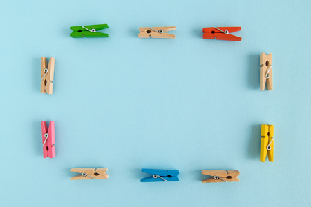 Frame from wooden colorful pins on the blue background with copy space.