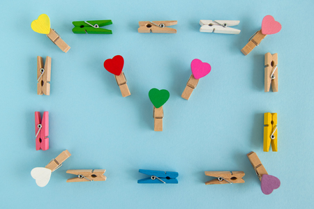 Frame from wooden colorful pins with hearts on the blue background, top view. Decorations for Valentine Day.