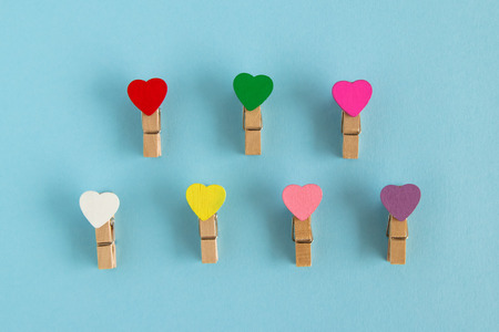 Wooden colorful pins with hearts on the blue background, top view. Decorations for Valentine Day.