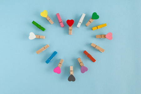 Heart-shaped frame from wooden colorful pins with hearts on the blue background with copy space. Decorations for Valentine Day.
