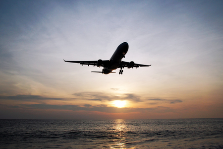 The beautiful view on a sea with plane in a sky during a colorful sunset. Phuket, Thailand. Stock Photo