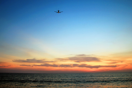 The beautiful view on a sea with plane in a sky during a colorful sunset. Phuket, Thailand. Foto de archivo
