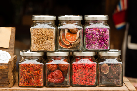 Glass jars with dry fruits and spices on a wooden table in a cafe. Stock Photo