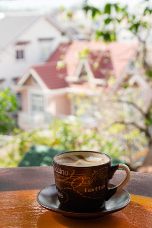Cup with hot milk coffee on a colorful wooden colorful table in a cafe on background of city view. Dalat, Vietnam.