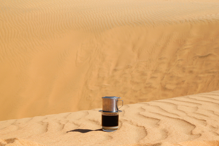 Drip Black Coffee in Vietnamese style with condensed milk on a red sand. Traditional method of making coffee. Breakfast in a desert.