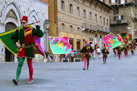 SIENA, ITALY - MAY 27, 2012: People in traditional costumes with flags and drums are going on Piazza del Campo in Contrada Day.
