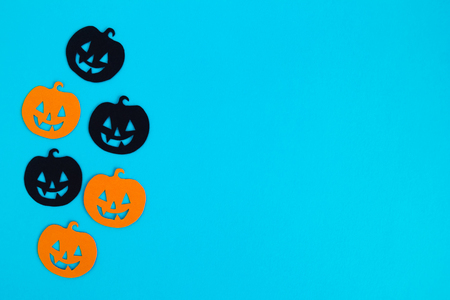 Holiday decorations for Halloween. Orange and black paper pumpkins on a blue background with copy space, top view. Stock Photo