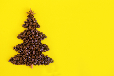 Winter composition with Christmas tree made by coffee beans and decorated anise star and cinnamon stick on a yellow background, flat lay. Greeting card for New Year with copy space.