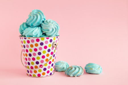 Small colorful bucket filled with blue meringue on a pink pastel background. Minimal concept with copy space.